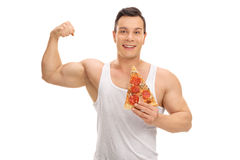 Man holding a slice of pizza and flexing his bicep Royalty Free Stock Photography