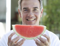 A man holding a slice of watermelon royalty free stock photography