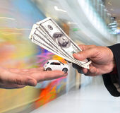 Man holding small car,another man holding dollar bills Royalty Free Stock Photos