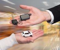 Man holding small car key, woman holding small car Royalty Free Stock Photo