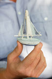 Man holding a small toy sailing boat - concept for sailing or cr Royalty Free Stock Photography