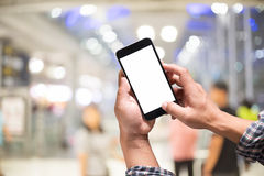 Man holding smart phone with blurred airport terminal background. Blank screen for Graphic display montage Stock Photography