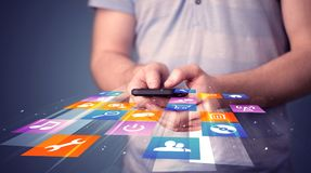 Man holding smart phone with colorful application icons. Comming out Royalty Free Stock Images