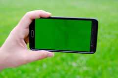 Man holding smart phone in hands against green spring background Stock Photos