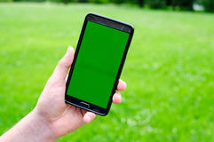 Man holding smart phone in hands against green spring background Stock Photo