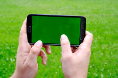 Man holding smart phone in hands against green spring background Royalty Free Stock Photos