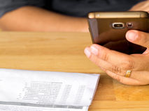 A man holding smart phone for using online banking app. For paying credit card bill.At on the wood table in the the backyard Royalty Free Stock Photos