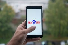 Man holding smartphone with Baidu logo with the finger on the screen. London, United Kingdom, october 3, 2017: Man holding smartphone with Baidu logo with the stock images