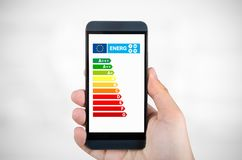 Man holding smartphone with energy efficiency chart. Savings in home concept stock photos