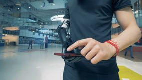 A man is holding a smartphone in his futuristic bionic prosthetic hand. Man of future concept. A man is holding a smartphone in his prosthetic hand. 4K