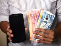 Man holding a smartphone and Philippine peso bills Royalty Free Stock Images