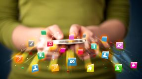Man holding smartphone with technology application icons. Comming out Stock Photo