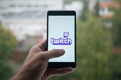 Man holding smartphone with Twitch logo with the finger on the screen. London, United Kingdom, october 3, 2017: Man holding smartphone with Twitch logo with the Royalty Free Stock Image