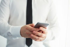 Man holding a smartphone and writing Royalty Free Stock Photo