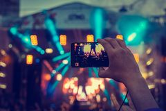 Man holding smartphones in hands and photographing and shoots a video. Taking photo on front stage on summer outdoor music concert. Festival royalty free stock photo