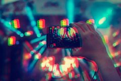 Man holding smartphones in hands and photographing and shoots a video. Taking photo on front stage on summer outdoor music concert. Festival. Digital signal stock photos