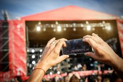 Man holding smartphones in hands and photographing. Taking photo on front stage on summet. Royalty Free Stock Image