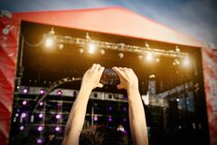Man holding smartphones in hands and photographing. Taking photo on front stage on summet. Stock Photos