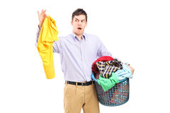 Man holding a smelly blouse and a laundry basket Stock Photo