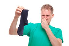 Man holding smelly socks and clogged nose Royalty Free Stock Photos