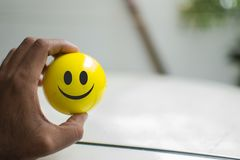 Man holding a smiley ball in hand royalty free stock image