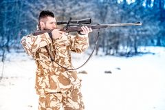 Man holding a sniper rifle and aiming at enemy on the battlefield Stock Photography