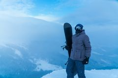 A man holding a snowboard in hand. snowboarder in the mountains stock image