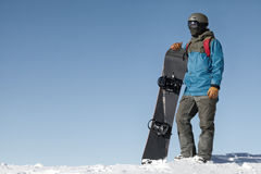 Man holding snowboard and taking a look at landscape at the top of mountains with blue sky on background. Filtered image: cross pr. Man holding snowboard and Royalty Free Stock Photography