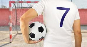 Man holding a soccer ball. Cropped rearview image of a young player man holding a soccer ball under his arms at empty football court in background Stock Photo