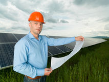 Man holding solar panel station plans Stock Image