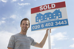 Man Holding Sold Sign Against Sky Stock Images