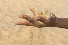 Man holding some sand in the hand: drought and desertification Stock Photos