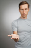 Man holding something blank in his hand on a grey background. Royalty Free Stock Photo