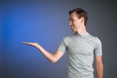Man holding something on his palm. Stock Photography