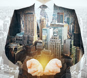 Man holding something multiexposure. Businessman holding something in palms on abstract city background. Double exposure Royalty Free Stock Photo