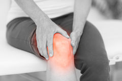 Man holding sore knee. Mid section of man holding sore knee Royalty Free Stock Images
