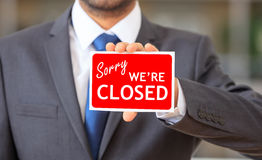 Man holding a sorry we are closed sign. Man holding a red sorry we are closed sign Royalty Free Stock Photography