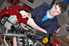 Man holding a spanner over a car engine. Close-up of mechanic repairing an engine in garage Royalty Free Stock Photo