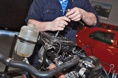 Man holding a spanner over a car engine. Close-up of mechanic repairing an engine in garage Royalty Free Stock Images