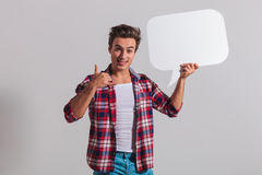 Man holding speech bubble and makes the call me gesture Stock Image