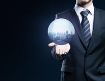 Man holding sphere with city. Businessperson holding abstract sphere with city on dark background Stock Image