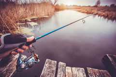 Man holding spinning rod on the river. fishing Stock Photography