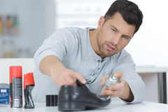 Man holding spray in front boots Stock Photography