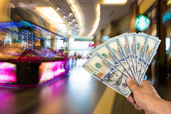 Man holding stack of dollar bills. At shopping mall stock images