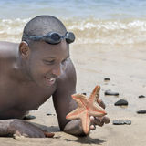 Man holding a starfish in the hand on a golden san Stock Images