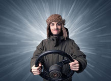 Man holding steering wheel. Young man holding black steering wheel with white lines behind him Royalty Free Stock Image
