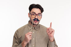 Man holding stick with mustache and pointing finger up. Portrait of a man holding stick with mustache and pointing finger up isolated on a white background Royalty Free Stock Photo