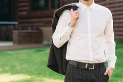 Man holding suit jacket over shoulder, free space Stock Photos