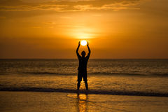 Man Holding The Sun. Silhoutted man on beach holding sun (sunset) between hands Royalty Free Stock Photo