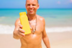 Man holding sunscreen bottle. Focus on the sample product bottle. Man holding sunscreen bottle on the beach. Focus on the sample product bottle royalty free stock photo